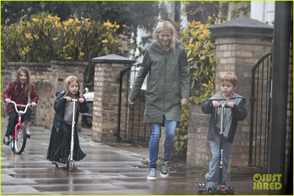 gwyneth paltrow kids scooting in the rain 022656171