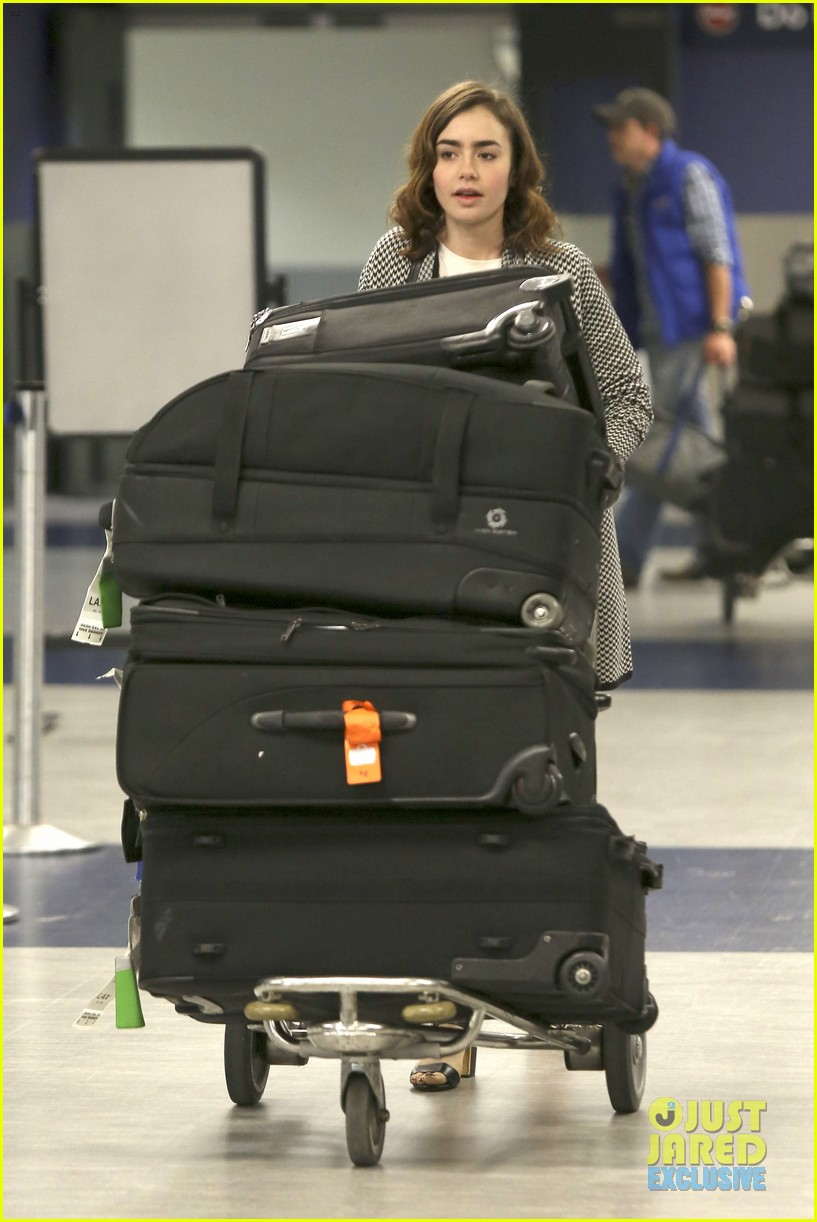 lily collins pushes giant luggage cart after mortals tour 12