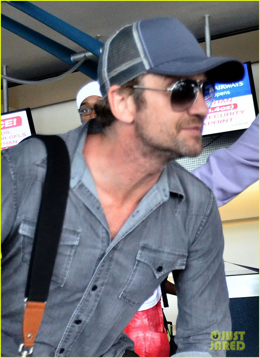 gerard butler ducks under ropes at barbados airport 06