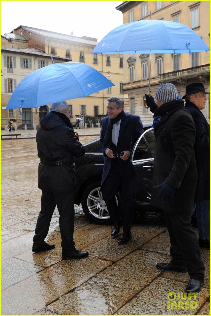 matt damon george clooney get personal umbrella holders in milan 08
