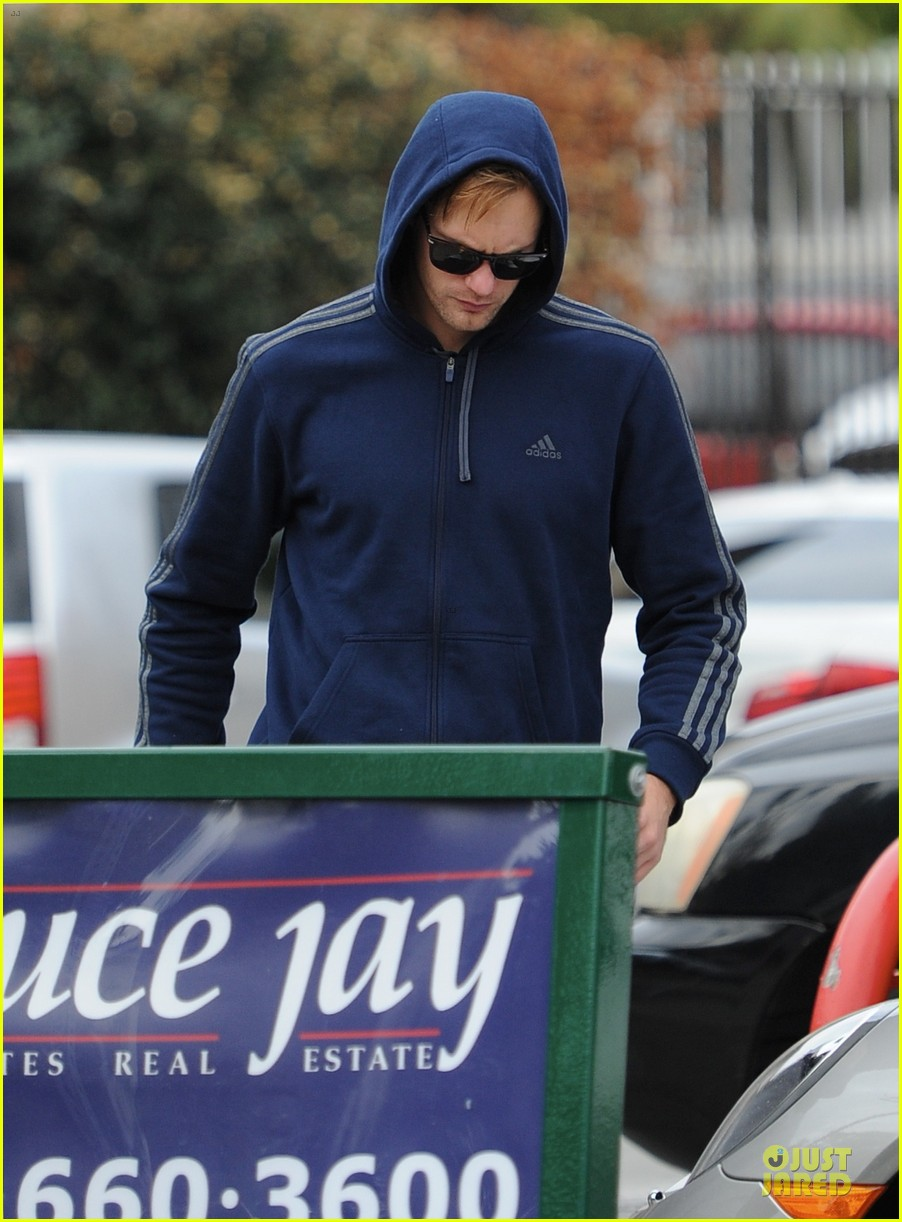 alexander skarsgard hides under a hoodie at gas station 02