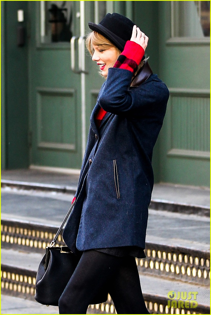 taylor swift holds onto her hat before it flies off her head 01