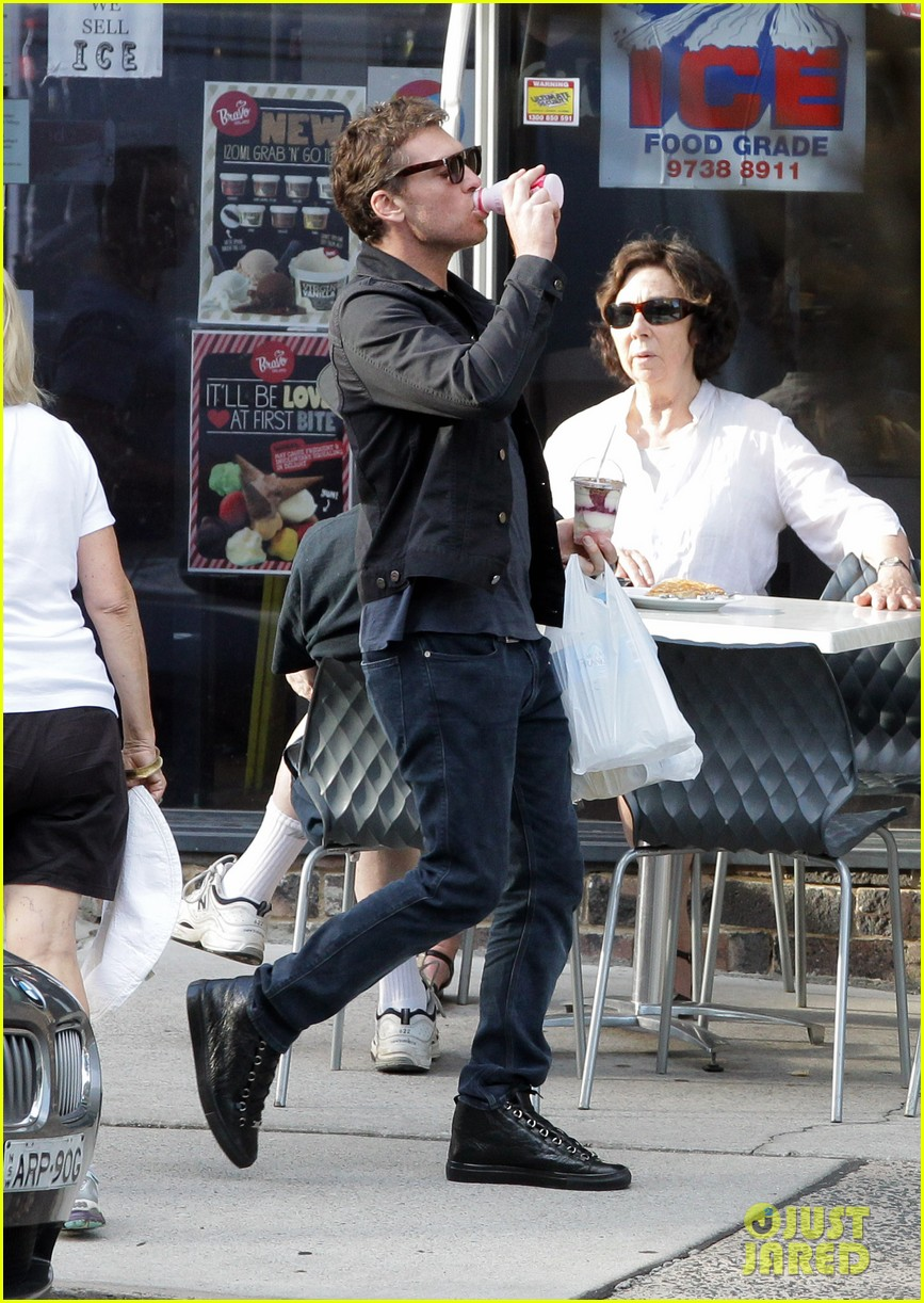 sam worthington juggles bags beverages in sydney 03