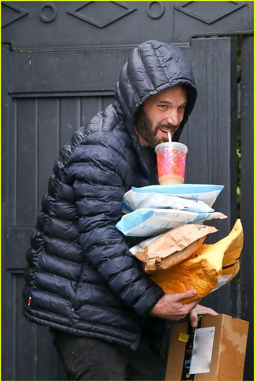 Ben Affleck balancing his coffee on packages