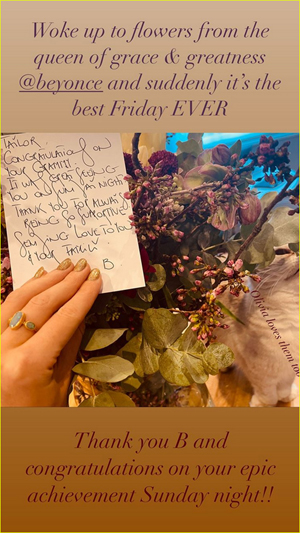 Taylor Swift holds a note in a flower bouquet