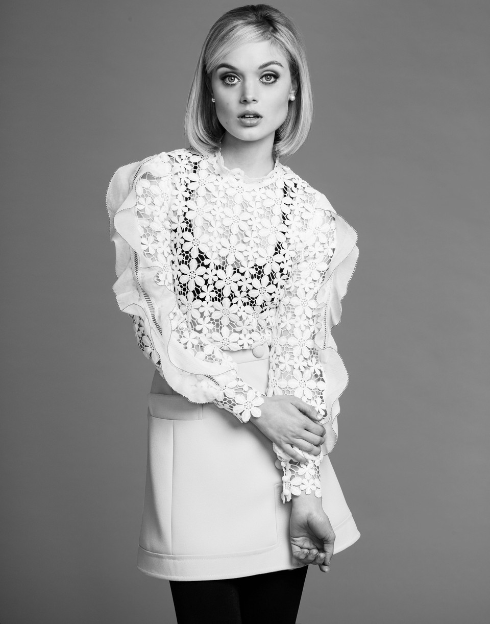 Bella Heathcote posing for a black and white portrait in a sheer lace top