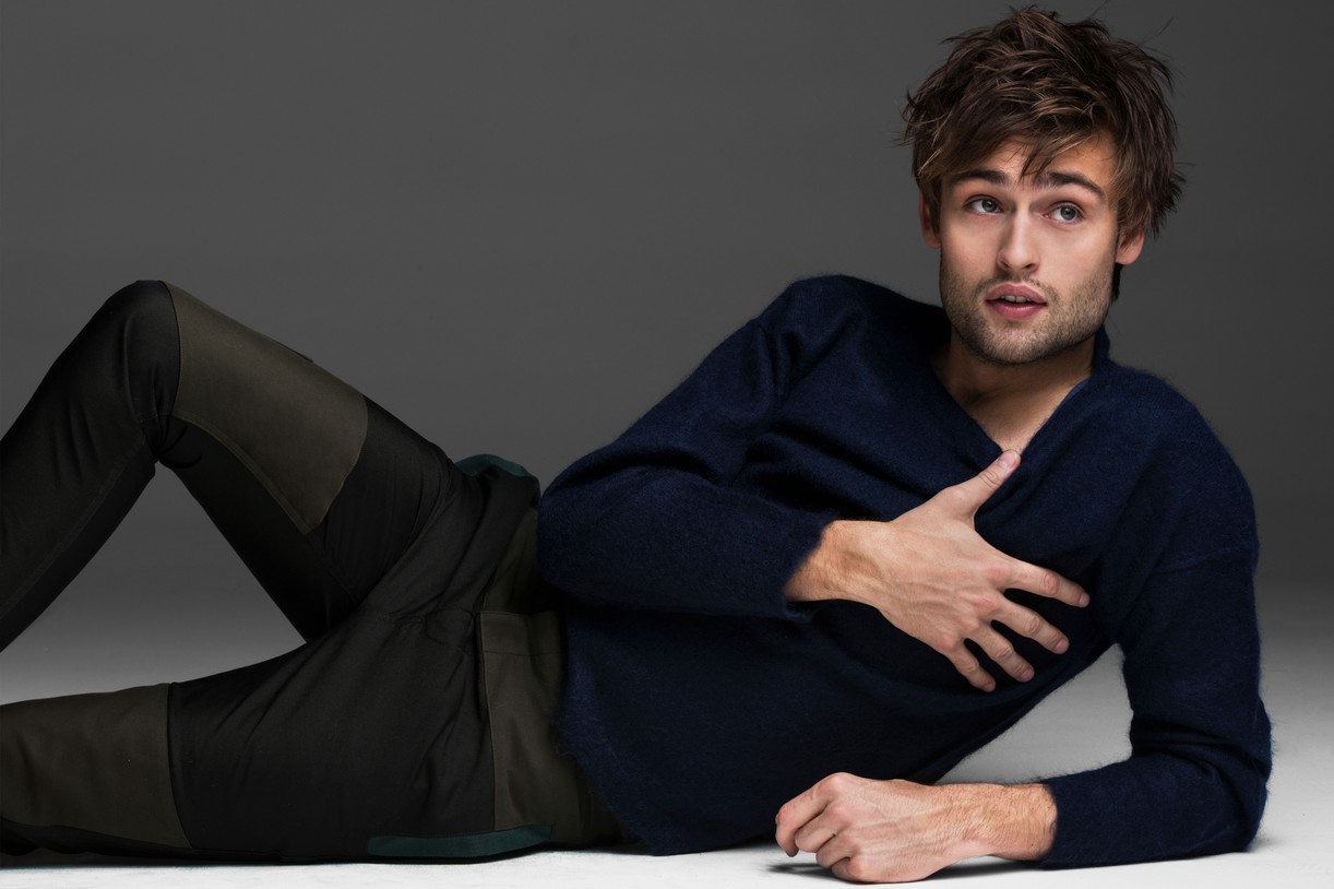 Douglas Booth lays on the ground with his thumb pulling down his shirt