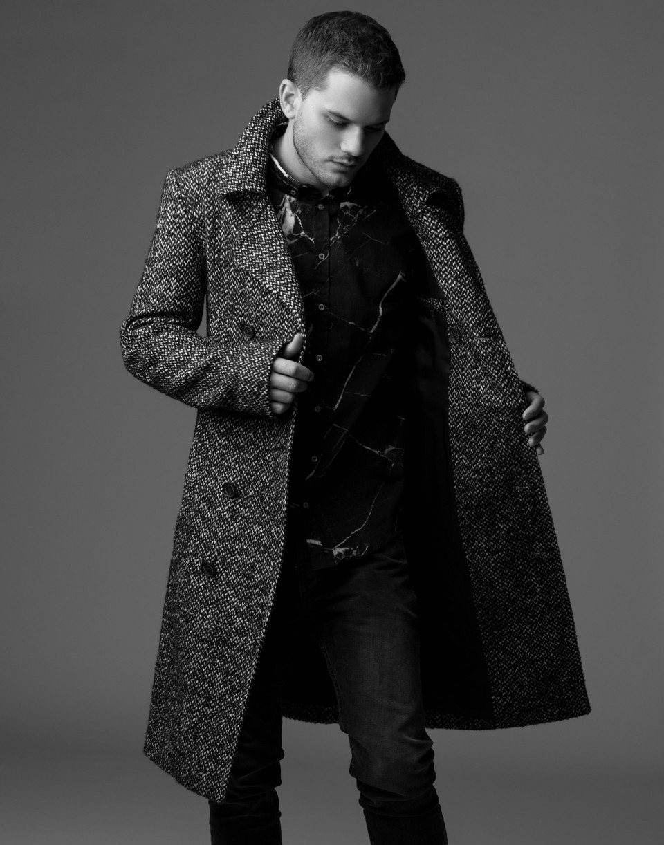 Jeremy Irvine standing and holding his coat open