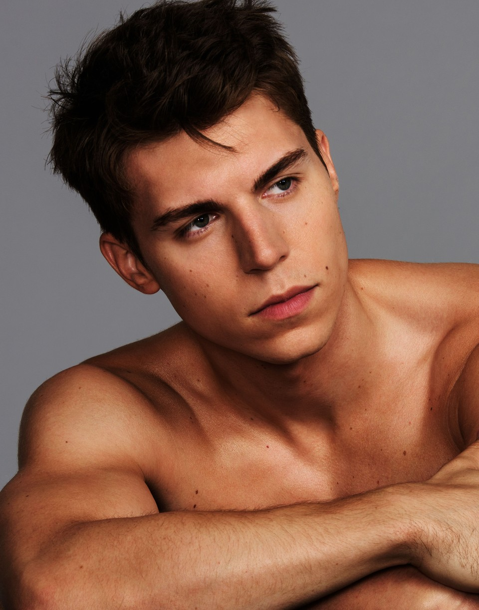 Nolan Funk shirtless with his arms crossed on the table