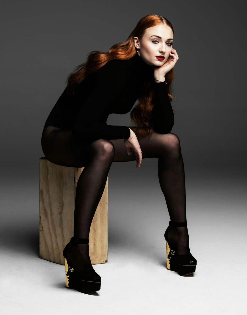 Sophie Turner sits on a wooden block while wearing a bodysuit and tights