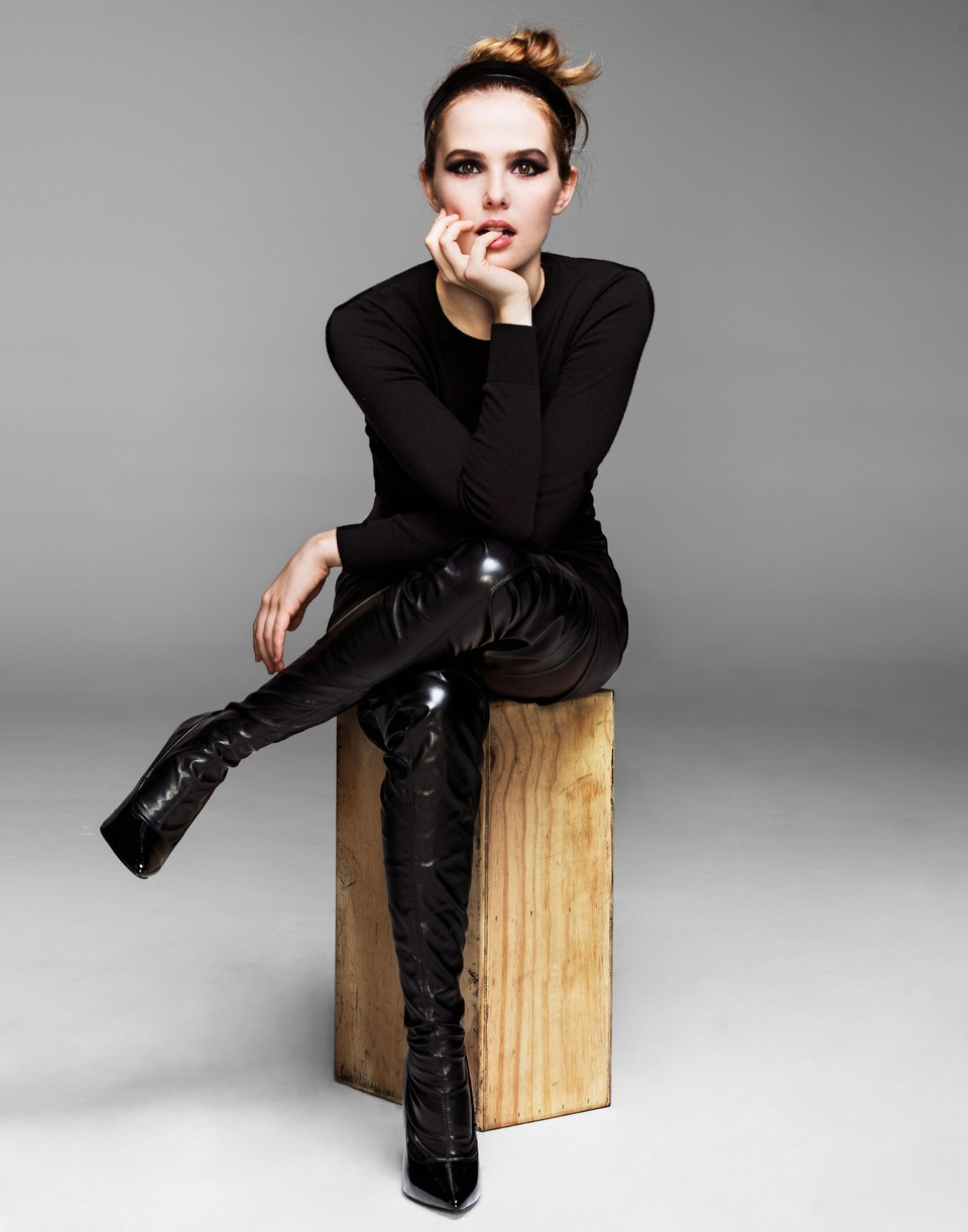 Zoey Deutch sits on a wooden block in a fierce black outfit with dark eye shadow