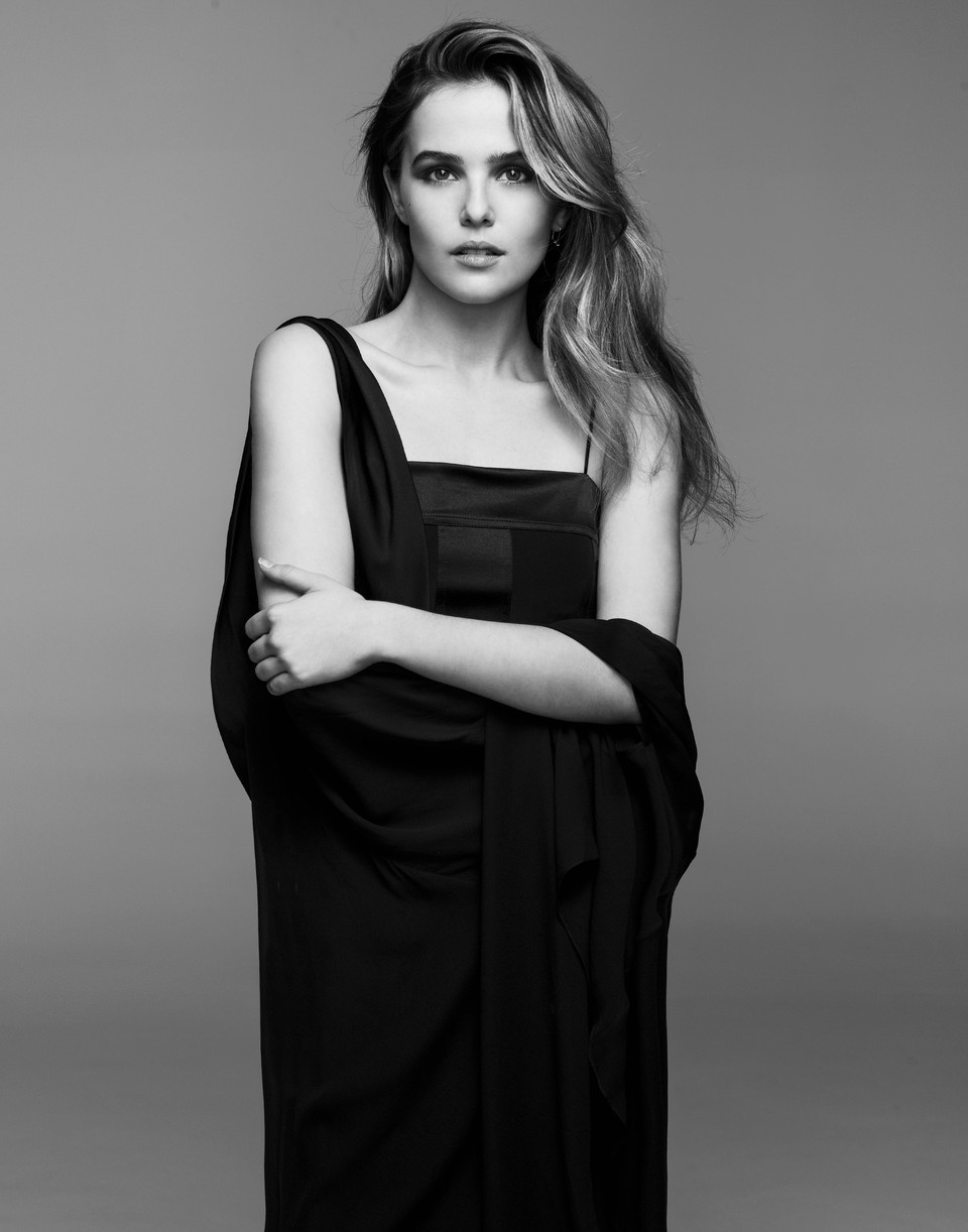 Zoey Deutch is pictured in black and white wearing a cape draped over her dress